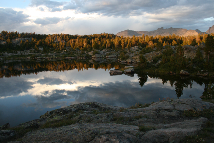 A large glassy lake surrounded by rocks reflects the sky above and the tree line along its shores.